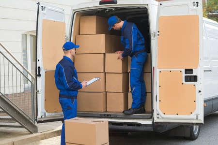the clipboard: Hombre de salida descargando cajas de cartón del camión mientras colega escrito en el portapapeles Foto de archivo