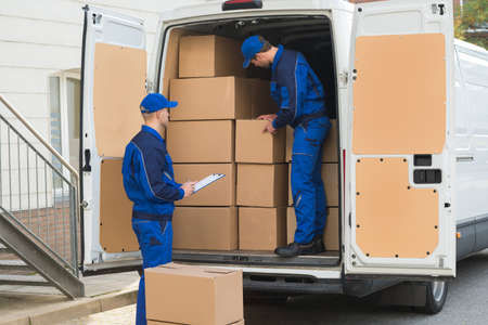 Delivery man unloading cardboard boxes from truck while colleague writing on clipboard