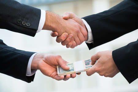 bribing: Cropped image of businessman shaking hand while bribing partner outdoors