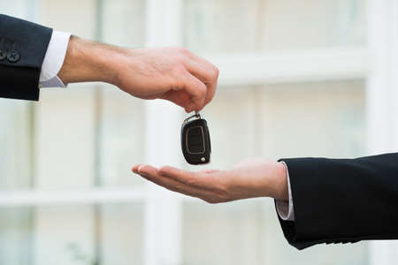 key: Cropped hands of car dealer giving keys to businessman outdoors