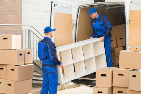 Young male movers unloading furniture and cardboard boxes from truck on street