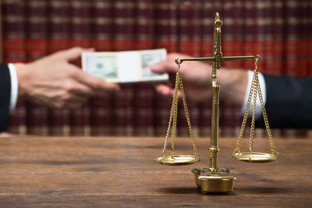 Justice scale on table with judge taking bribe from client in background at courtroom