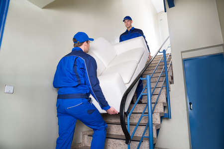 Male movers carrying sofa while climbing steps at home