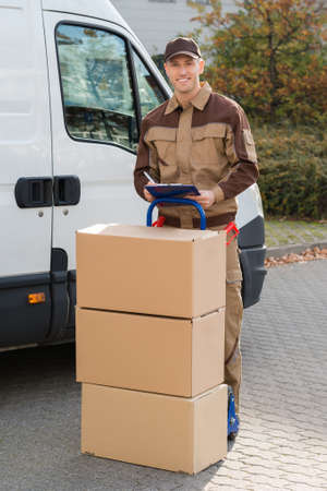 clipboard: Portrait of confident delivery man with parcels and clipboard standing on street
