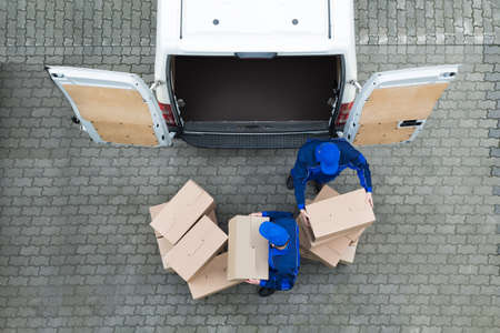 unload: Directly above shot of delivery men unloading cardboard boxes from truck on street Stock Photo