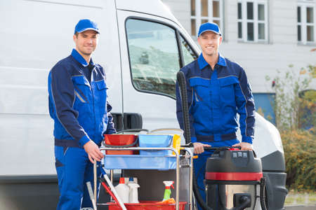 Portrait of happy janitors with cleaning equipment standing against truck 写真素材