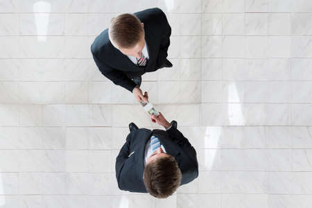 Directly above shot of businessman bribing colleague in office