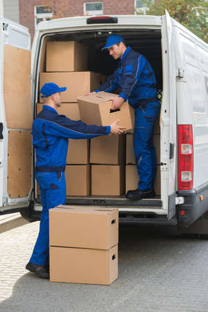 removal van: Full length of delivery men unloading cardboard boxes from truck