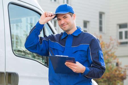 Portrait de livraison homme en uniforme, tenue, presse-papiers par camion Banque d'images