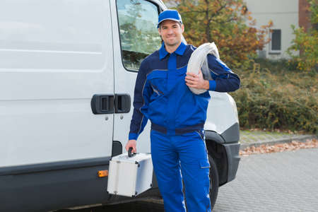 Portrait of confident electrician with cable coil and toolbox standing outside truck Standard-Bild