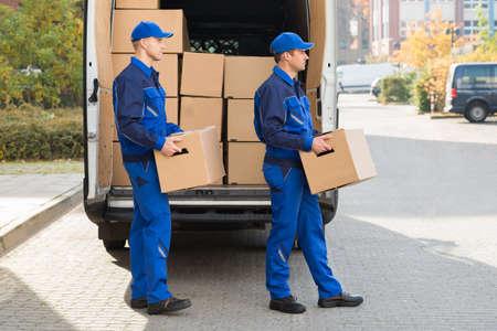 Lachende jonge levering man die kartonnen dozen tijdens het lopen buiten truck