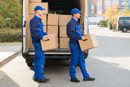 moving truck: Smiling young delivery men carrying cardboard boxes while walking outside truck Stock Photo