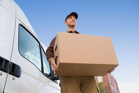 Low angle portrait of young delivery man carrying cardboard box by truck against sky