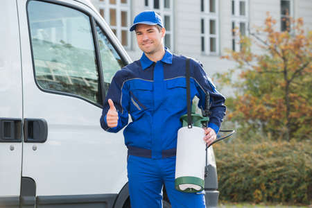 worker man: Portrait of smiling pest control worker showing thumbsup while standing by truck