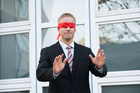 waistup: Blindfolded young businessman gesturing while standing against window outdoors