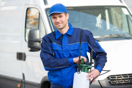 exterminator: Portrait of confident pest control worker with pesticide against truck Stock Photo