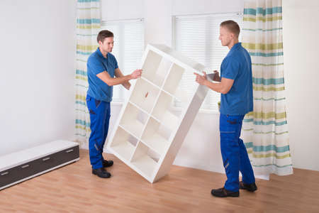 Young male movers carrying shelf at home Stock Photo