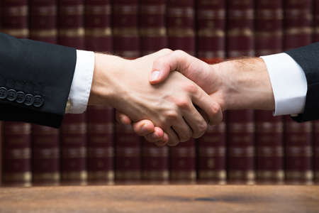 Cropped image of judge and client shaking hands against books at courtroom