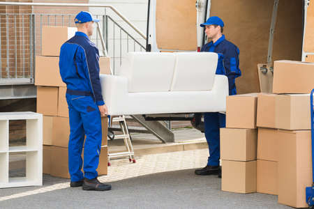 Longueur totale des jeunes déménageurs masculins portant un canapé en dehors camion sur la rue Banque d'images