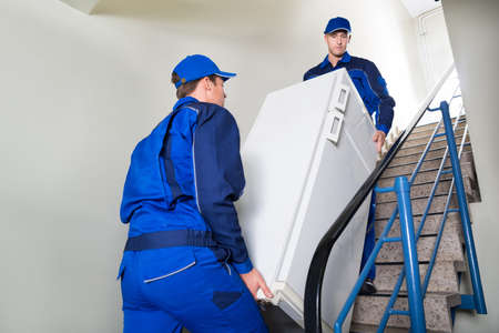 Side view of movers carrying refrigerator while climbing steps at home