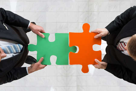assembling: Directly above shot of businessmen assembling jigsaw puzzle representing teamwork in office