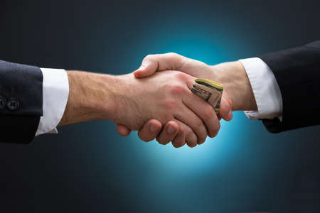 Cropped image of businessman shaking hands while giving bribe to partner against blue background