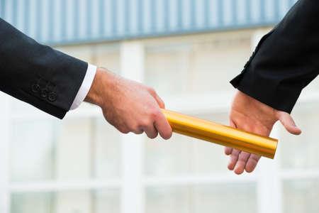 屋外の同僚に黄金リレーのバトンを渡すのビジネスマンの手をトリミング