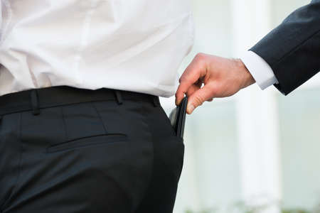 Cropped hand pickpocketing wallet of businessman outdoors