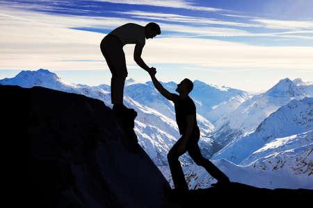 Silhouette junger Mann unterstützen männlichen Freund in Kletterfelsen Standard-Bild