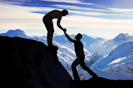 team vision: Silhouette young man assisting male friend in climbing rock