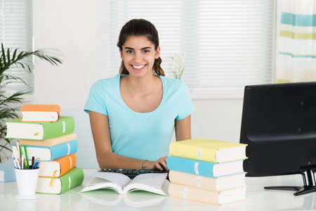 keyboards: Portrait of happy female student using computer while studying at table in home office