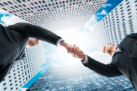 directly below: Directly below shot of businessmen shaking hands against office buildings Stock Photo