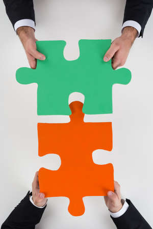 representing: Cropped image of businessmen assembling jigsaw puzzle representing teamwork at desk