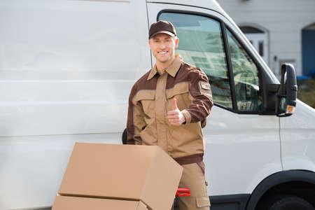 handtruck: Portrait of confident delivery man pushing parcels on handtruck against van Stock Photo