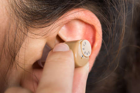 impaired: Cropped image of young woman wearing hearing aid at home