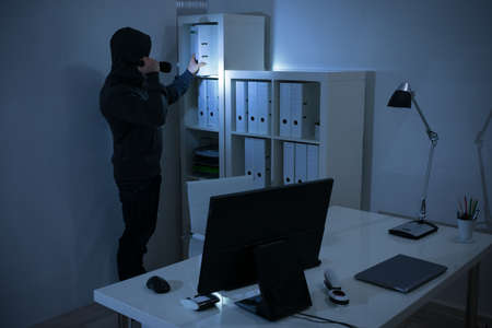 intruding: Robber with flashlight searching for documents in office at night Stock Photo