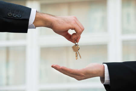 house keys: Cropped hand of real estate agent giving house keys to businessman outdoors Stock Photo