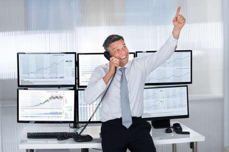 Szczęśliwy mężczyzna przedsiębiorcą czas, wskazując w górę podczas korzystania z telefonu na biurku w biurze