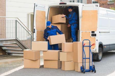 Young delivery men unloading cardboard boxes from truck on street