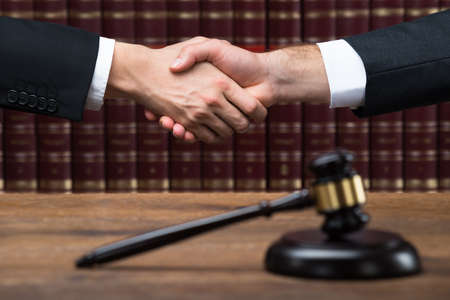 Gavel on wooden table with judge and client shaking hands in background at courtroom Foto de archivo