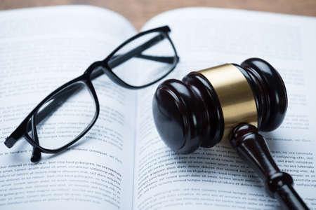 Erhöhte Ansicht der Hammer und Brillen auf offenen Rechts Buch im Gerichtssaal Lizenzfreie Bilder
