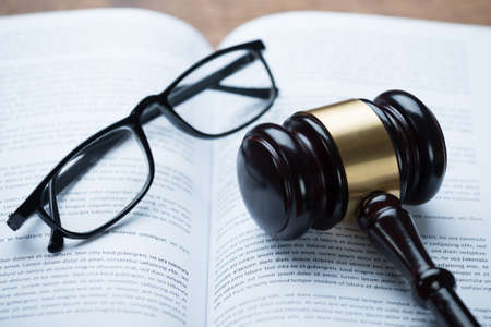 autoridad: Vista de ángulo alto del mazo y anteojos en el libro legal abierto en la sala de audiencias