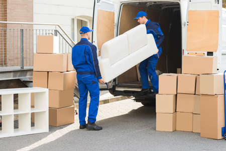 unloading: Young male movers unloading sofa from truck on street Stock Photo