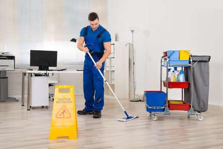 Full length of male janitor mopping floor in office Foto de archivo