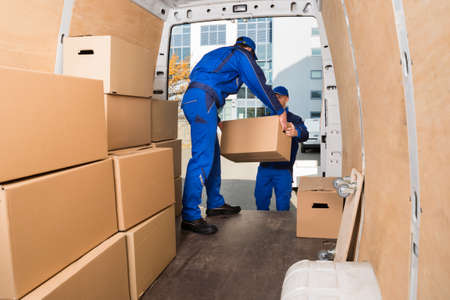 Young delivery men loading cardboard boxes in truck Stockfoto