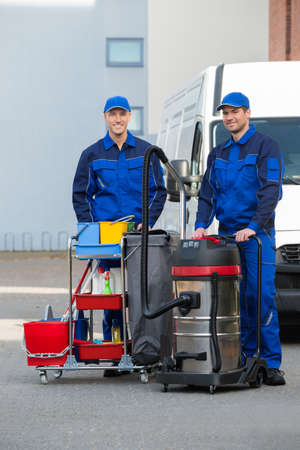 Portrait of confident male janitors with cleaning equipment standing on street 写真素材
