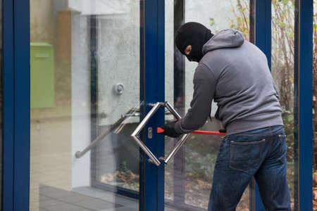 crowbar: Hooded man using crowbar to open glass door