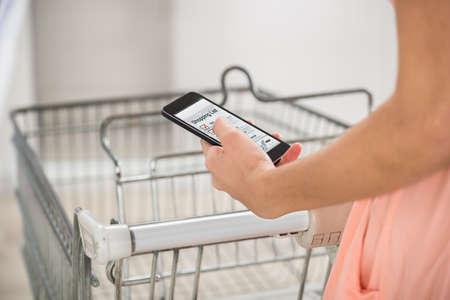 carretilla de mano: Mujer con la lista de la compra de cheques carretilla de mano en el teléfono inteligente en el supermercado