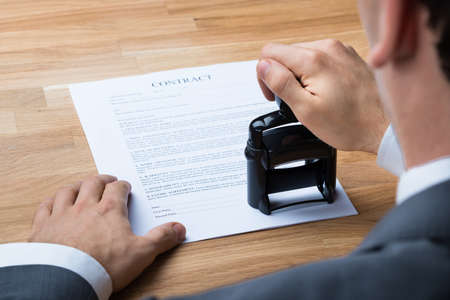 authority: Cropped image of businessman stamping contract document at office desk