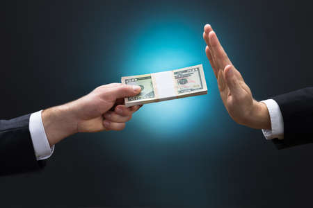 bribe: Cropped hand of businessman refusing to take bribe from partner against blue background